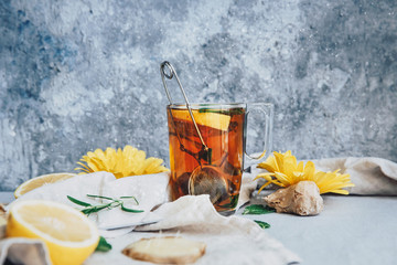 Glass mug of ginger tea with  lemon, ginger  and mint on rustic table