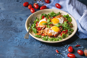 Traditional Israeli Cuisine dishes Shakshuka. Fried egg with vegetables tomatoes and paprika in ceramic plate with cloth, herbs and ingredients above over blue texture background. Copy space.