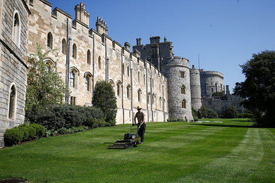 A groundsman mows the lawn outside Windsor Castle in the sun, in Windsor