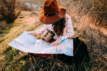 Traveler beautiful girl with a hat looking at a map holding in her hand binoculars at sunset sitting on a background of mountains. She selects a place on the map. Concept photo travel, adventure