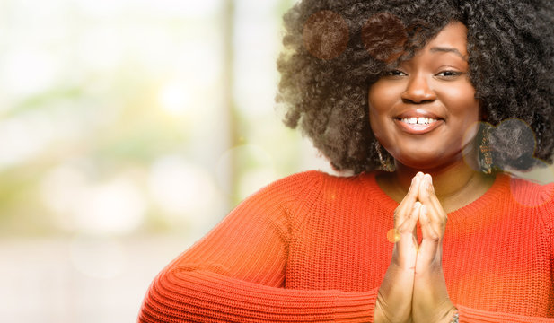 Beautiful african woman with hands together in praying gesture, expressing hope and please concept, outdoor