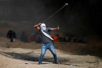 Demonstrator gestures as he hurls stones during clashes with Israeli troops at a protest at the Israel-Gaza border where Palestinians demand the right to return to their homeland, east of Gaza City