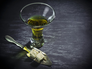 Glass of Absinthe with sugar cubes and spoon