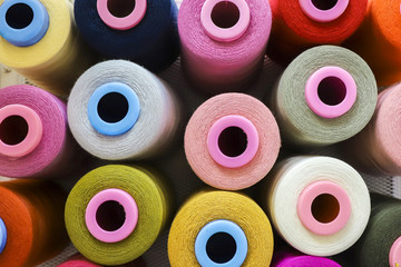 Sewing threads on spool, multicolored background.