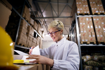 Young beautiful female worker is looking at her papers and smiling in factory storage room.