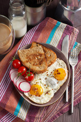 Healthy simple breakfast with bread toast, fried eggs and vegetables