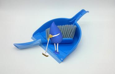 Foto von einem Kehrblech auf dem ein 3d Charakter eines Tropfenmännchens mit Besen fegt. 3d illustration