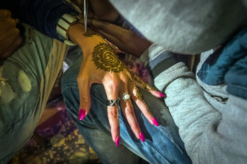 Artist drawing henna pattern on woman hand,