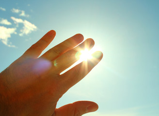 The man's hand covers the sun. The man closes the palm of sunlight. Close-up. Background.