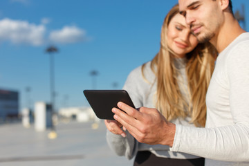 Young couple using digital tablet outdoor