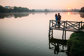 Walk the morning of a guy and a girl. Love story on the bridge. Young people by the lake.