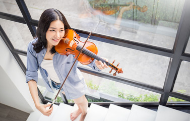 Portrait of beautiful young asian woman playing violin. Education leisure and recreation concept Wall mural