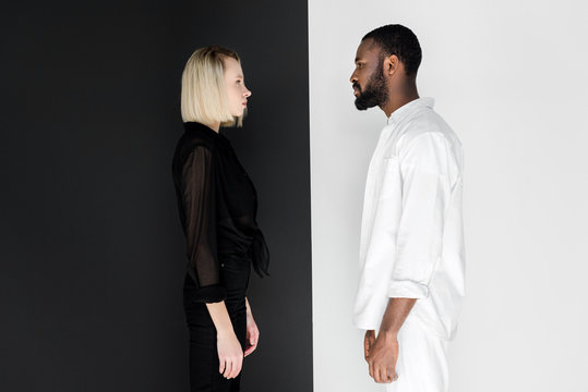 side view of african american boyfriend and blonde girlfriend looking at each other near black and white wall