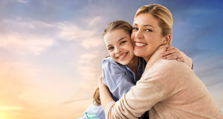 people and family concept - happy smiling mother hugging daughter over evening sky background