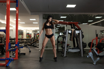 A beautiful sporty brunette is standing in the gym