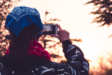A young girl in a blue shawl stands with her back and takes pictures of nature and mountains at dusk at sunset on a mobile phone.