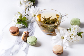 Glass cup of hot green tea with french dessert macaroons, spring flowers white magnolia and cherry blooming branches over white marble texture background.