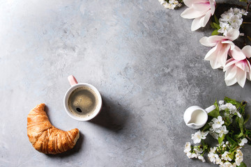 Pink mug of black espresso coffee, french croissant, cream and spring flowers magnolia, blooming cherry branches over grey texture background. Top view, space. Spring greeting card, wallpapers