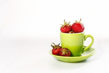 fresh juicy strawberries in green cup and saucer isolated on white background