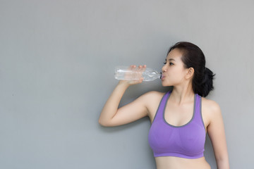 Young woman are drinking water after exercise.