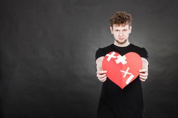 Very sad young man holding broken heart