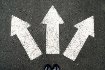 Three white arrows pointing in different directions on gray asphalt floor and black Shoes. Making decisions and making choices. Find your own way. Walking direction, crossroads, intersection, crossway