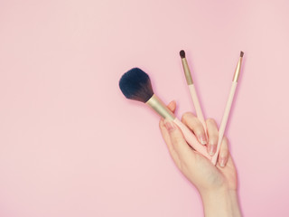 cosmetic and beauty concept from beauty asian hand hold and use cosmetic brush with isolated pink pastel background