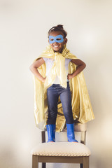 Little girl wearing yellow superhero cape