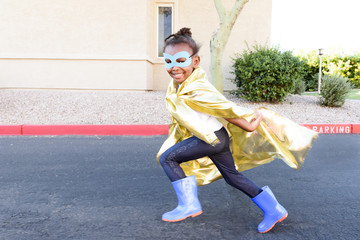 Little girl wearing yellow superhero cape and running along street
