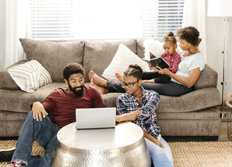 Family reading and and looking at laptop in living room