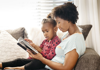 Mother and daughter reading book together on sofa