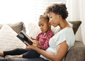 Mother reading book to young daughter on sofa
