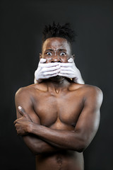 White hands cover the mouth of a black man