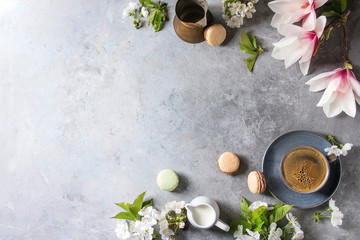 Blue cup of black espresso coffee french dessert macaroons, cream and spring flowers magnolia, blooming cherry branches over grey texture background. Top view, space. Spring greeting card, wallpapers
