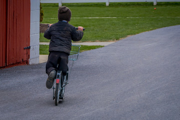 Unidentified little amish boy playing with his roller bikes or scootersin the backyard of his house