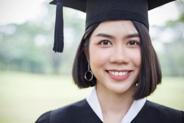 Closeup portrait of young asian woman outside the building on her graduated day. Face of cute asian girl with  Education success graduate concept banner
