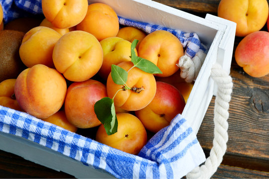 many fresh apricot with leaf in white wooden box