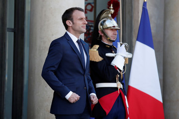 French President Emmanuel Macron waits for the arrival of Senegalese President Macky Sall at the Elysee Palace in Paris