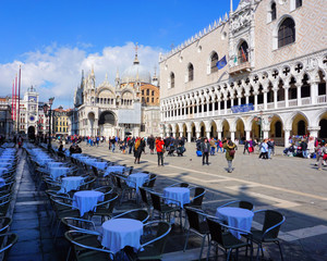 Venice, Veneto / Italy - March 2018: Tables sit mostly empty while tourists mill around St Mark's Square near Doge's Palace in Venice, Italy.