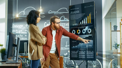 Female Developer and Male Statistician Use Interactive Whiteboard Presentation Screen to Look at Charts, Graphs and Growth Statistics. They Work in the Stylish Creative Office.