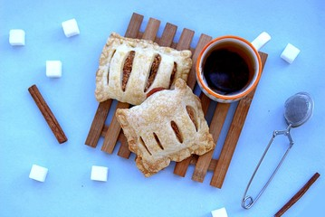 Baked pies made of puff pastry with apples and cinnamon