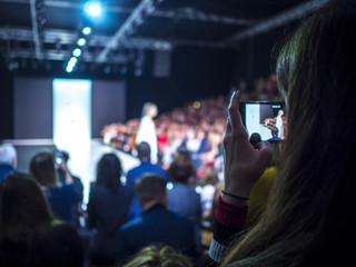 Woman holding phone during the fashion show