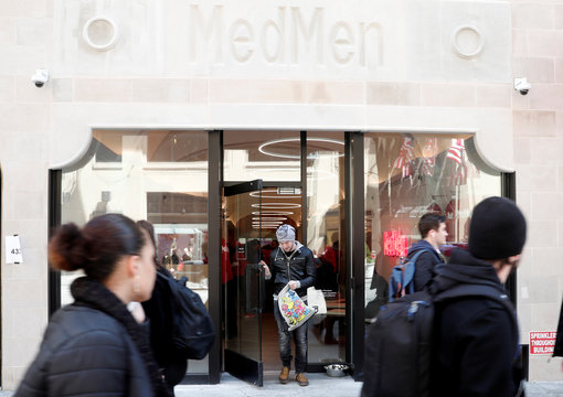 A man exits MedMen, a California-based cannabis company store serving medical prescription patients with cannabis products, on the store's opening day on 5th Avenue in Manhattan in New York City