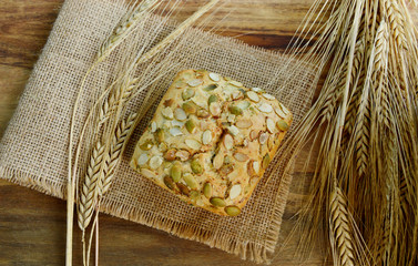 Pumpkin seeds bread with Wheat on the sack cloth on wooden background. homemade organic honey oat bread for healthy.