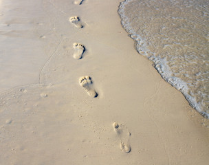 Barefoot walk chain on wet white sand. Beach view photo. Foot marks on beach.