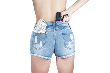 Woman pushes a gun in the back for a belt short with money in a pocket, close-up, isolated on a white background