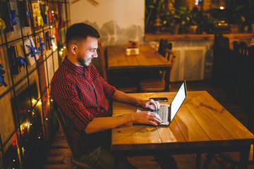 A young handsome Caucasian man with beard and toothy smile in a red checkered shirt is working behind a gray laptop sitting at a wooden table. Hands on the keyboard. In the evening at the coffee shop