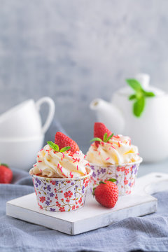 Homemade muffins or cupcakes with vanilla cream and fresh strawberries on the light grey background