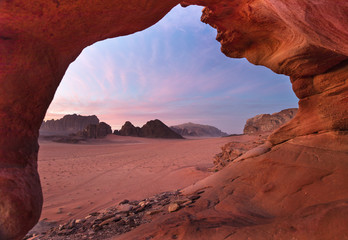 view through red stone arch to beautiful dusk in desert Wadi Rum in Jordan