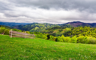 lovely rural scenery of Carpathians. beautiful landscape with grassy rural fields on hills in springtime. overcast sky over the mountains